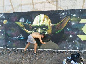 murales: erik spruzzando una bomboletta sulla sua opera