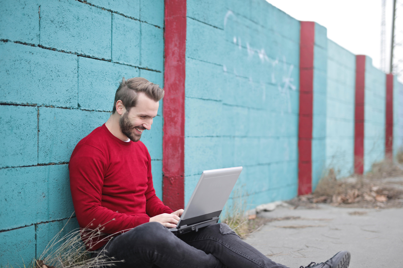 attività online: forse il giovane uomo che sorride con laptop sulle ginocchia la sta svolgendo