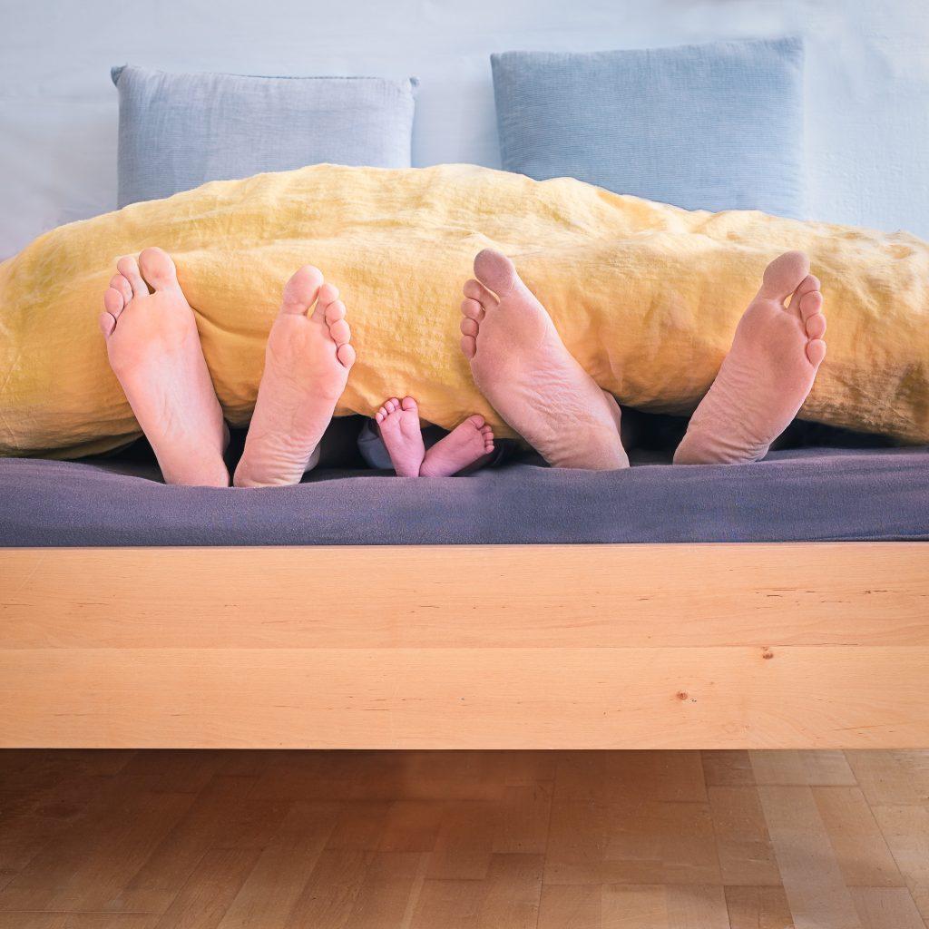 less is more: immagine dei piedi di mamma papaà e figlio che dormono insieme, n semplicità