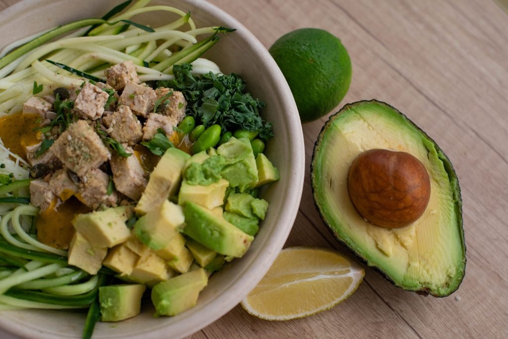avocado tagliato con un piatto di insalata a fianco