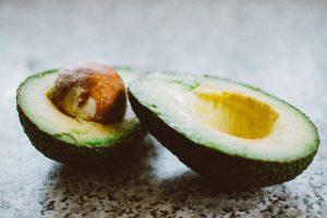 avocado tagliato in due con in evidenza il grosso nocciolo